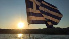Vacker solnedgång över Valtos Beach med grekiska flaggan i topp.