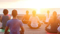 Yoga i solnedgången på Mexikos kust.